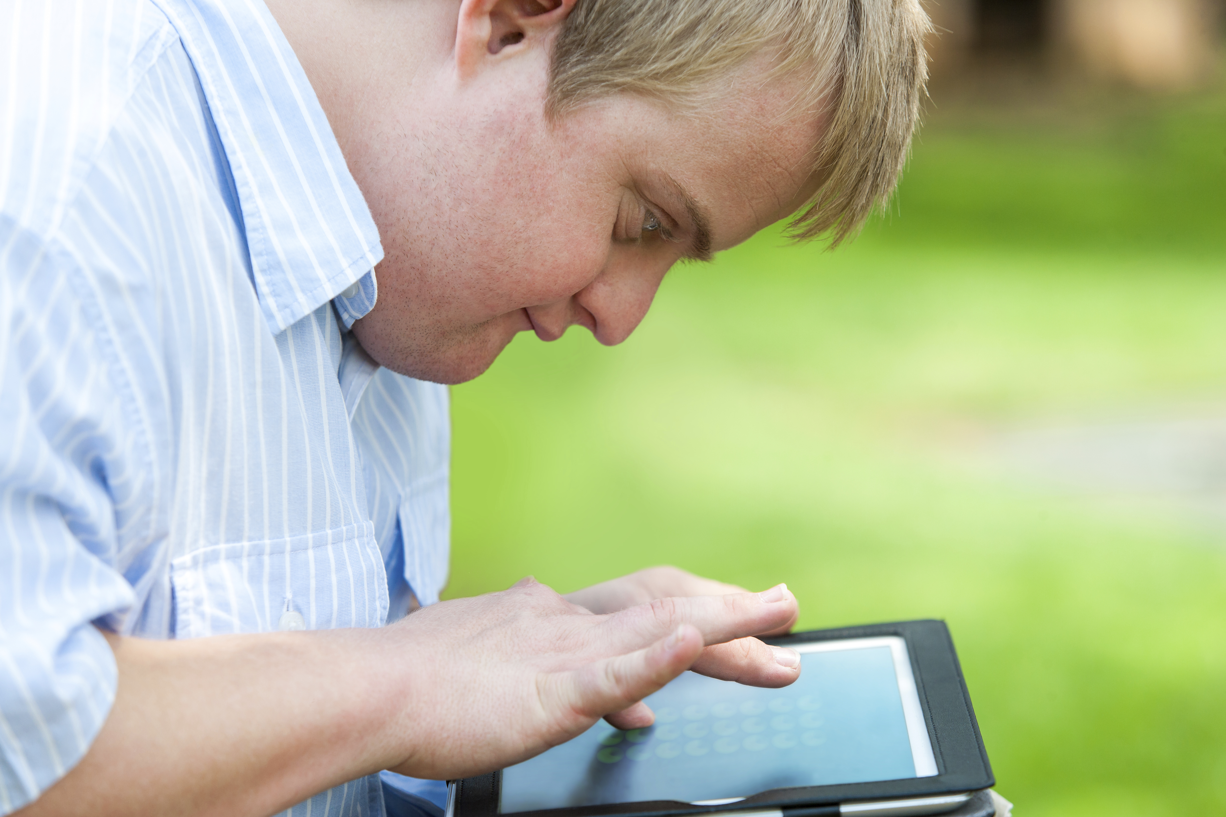 Young man taps a tablet screen