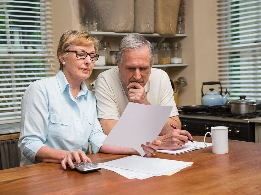 Older heterosexual couple sitting at the kitchen table reviewing important paperwork
