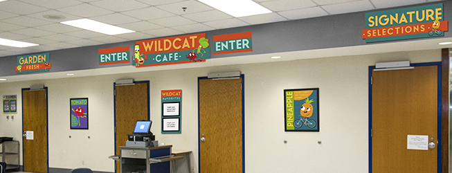 Cafeteria signs above entrance doors, orange and blue with fruits and vegetable nutrition characters
