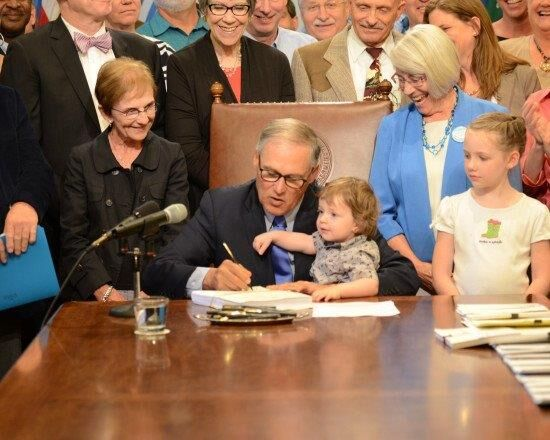Justice Bridge watching as Governor Inslee signs the legislation for the new Children's Department.