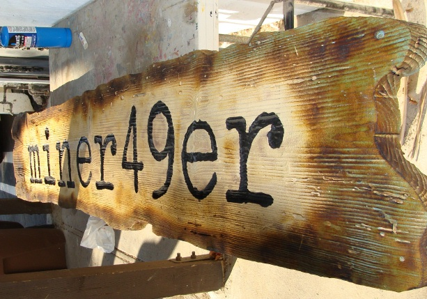 "SA28390 - Close-Up of Antique-Look Rustic Cedar Wood Sign for the ""Miner 49er"" retail Store"