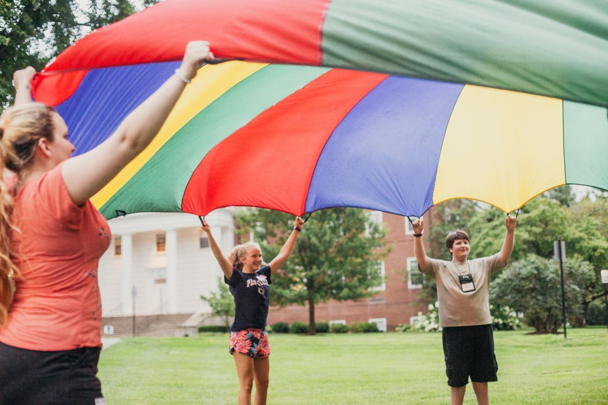 3 folks playing with a rainbow parachute