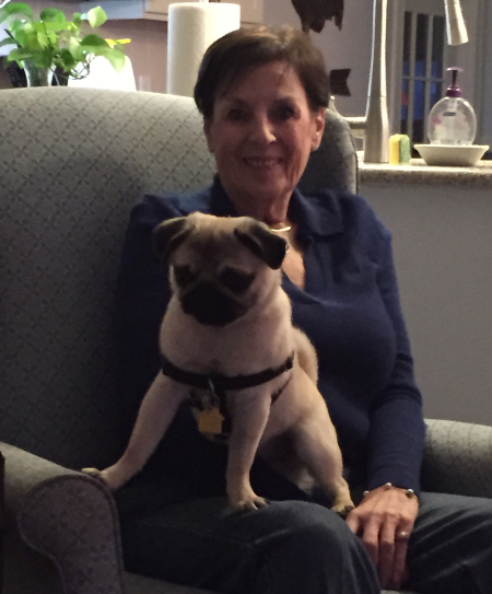 Mary O'Brien sitting in a chair, smiling and holding the pug, Luna.