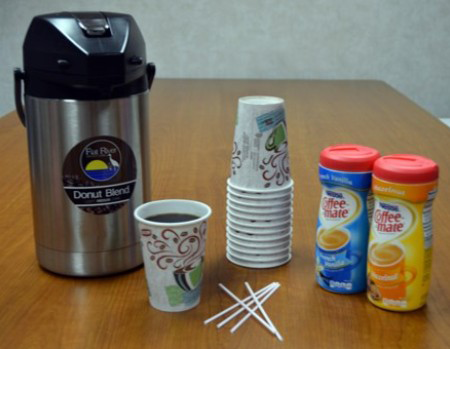 Coffee Pot Next to Cups and Creamer on Table
