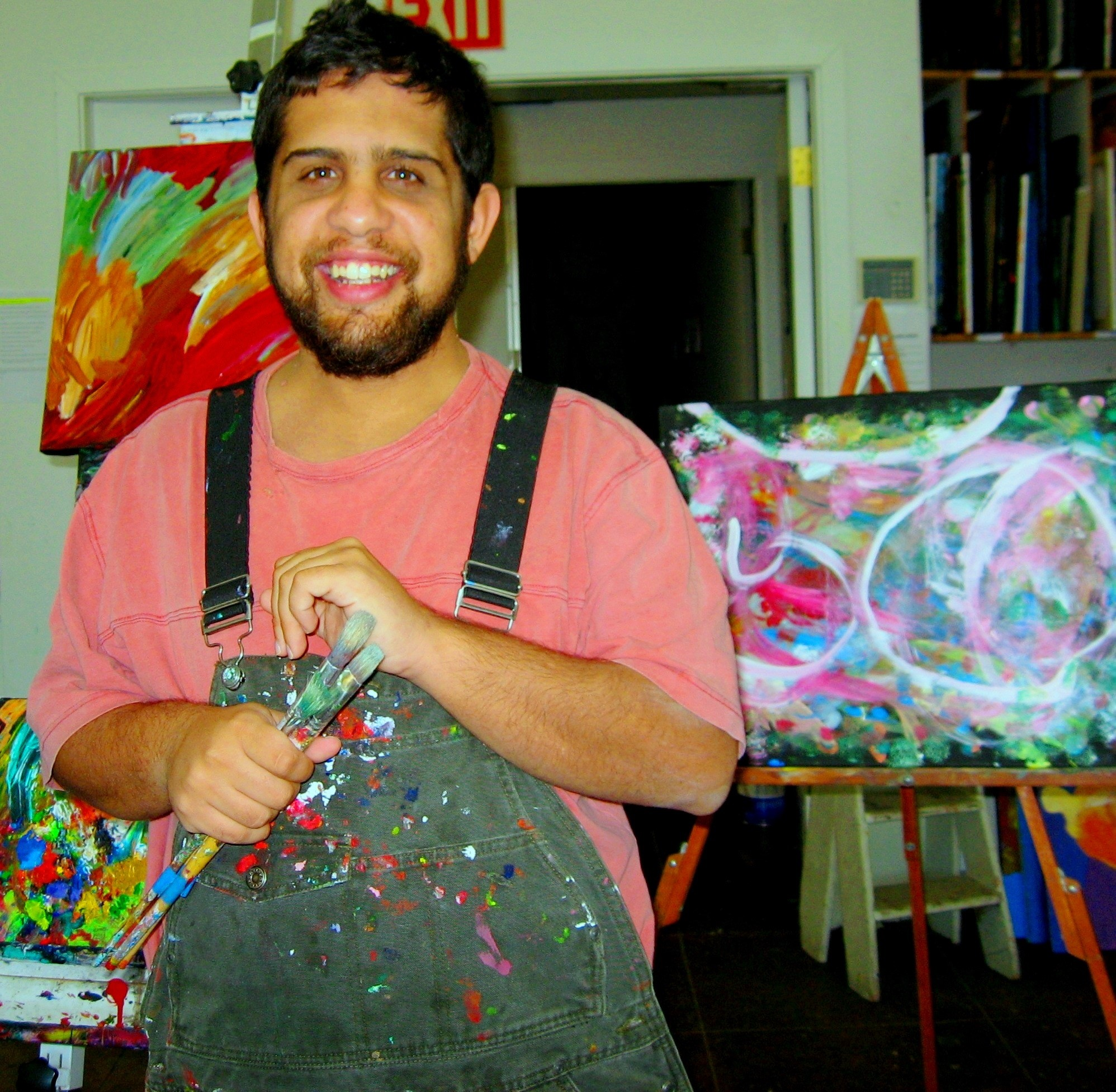 A man poses with paint brushes in front of his artworks.