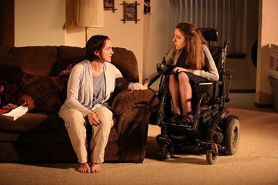 (L to R): Pamela Sabaugh is sitting on the couch and wearing comfortable clothing. Shannon DeVido is sitting in her power wheelchair, wearing shoes and a grey sweater. They are talking about their childhood.