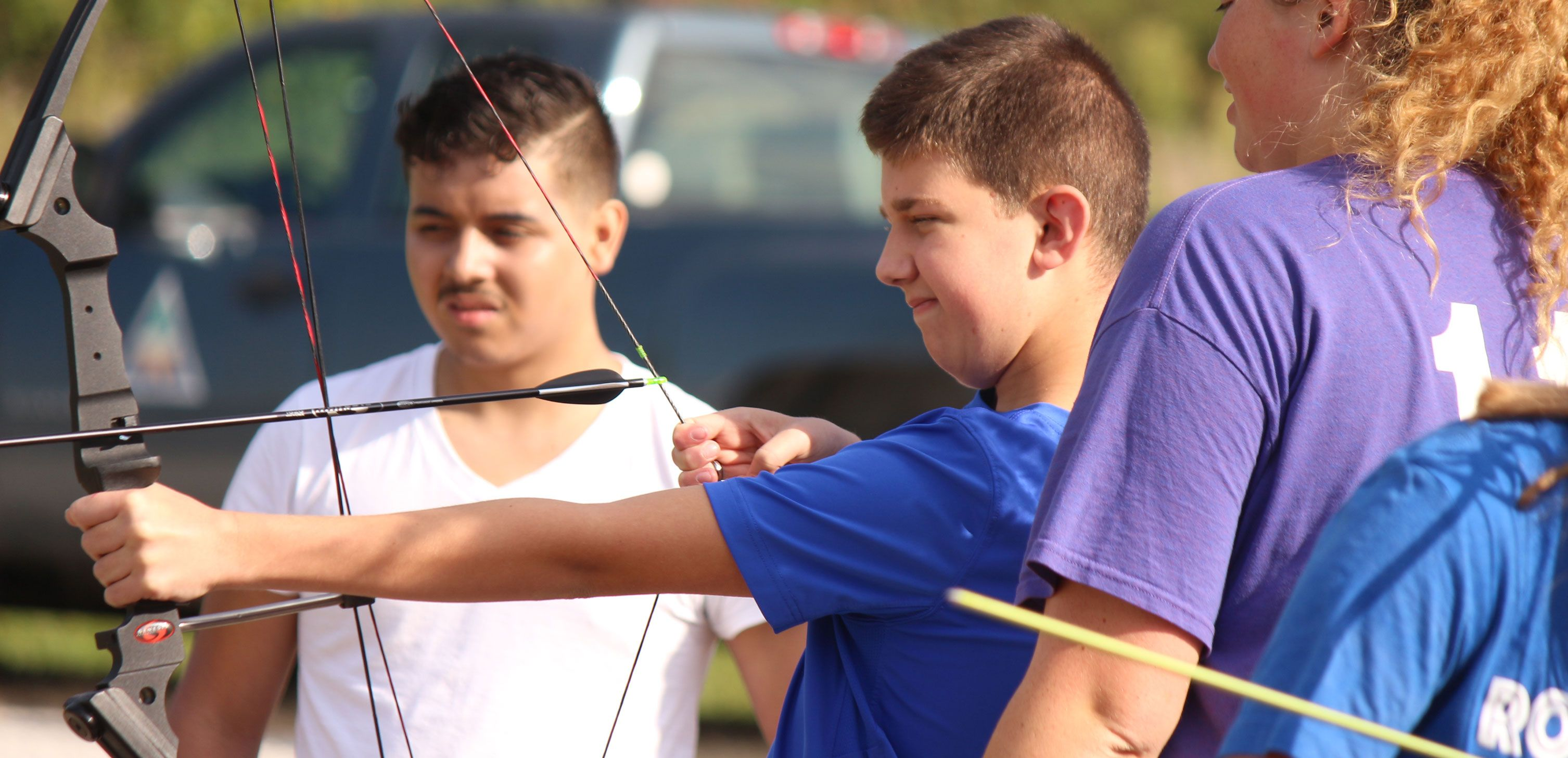 Young boy learning to shoot arrow