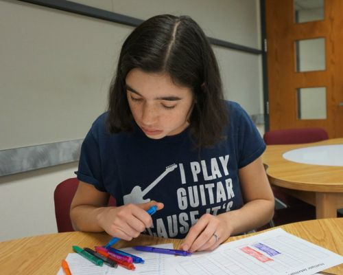 Student wearing I play guitar shirt working on an assignment