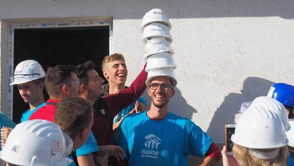 Group of volunteers stacking hard hats on a friend.