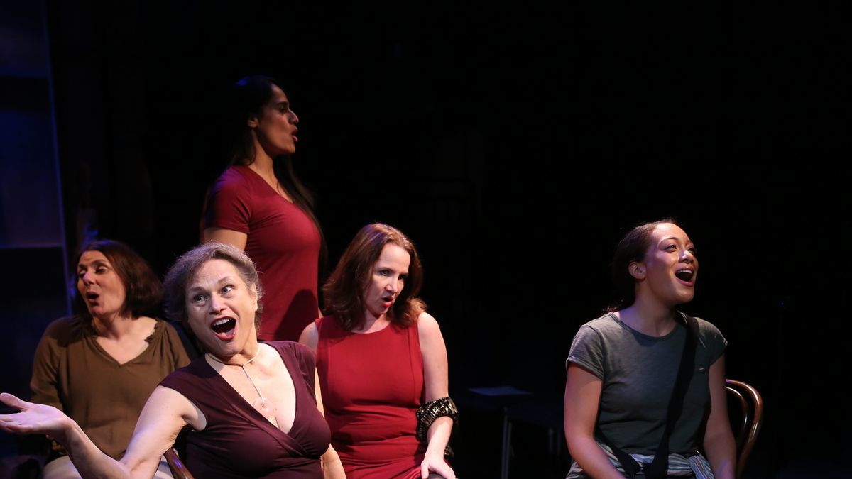 A picture of the female cast of Brecht on Brecht. They all are sitting on chairs and singing to something. They also have a spotlight on them.