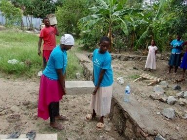 Two woman carrying cement block.