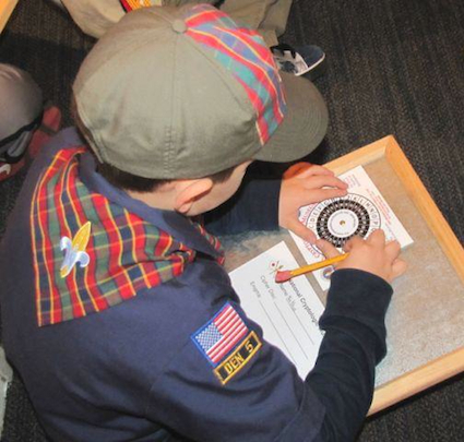 Webelo scout learns about ciphers with the cipher challenge at the National Cryptologic Museum
