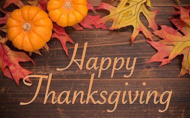"""Autumn leaves and pumpkins on a wooden table surrounding the phrase, """"Happy Thanksgiving."""""""