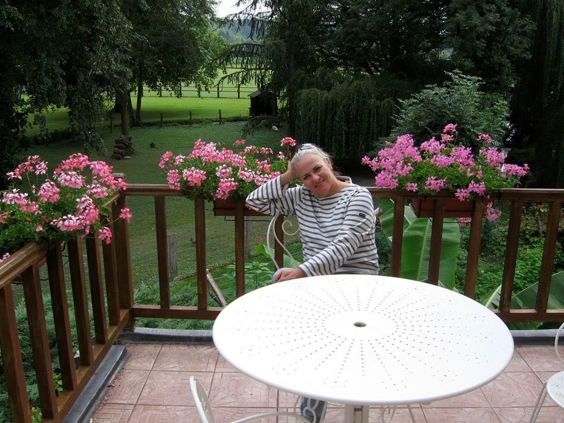 Moira sitting at a circular white table on a wood deck in front of green backyard with pink flowers