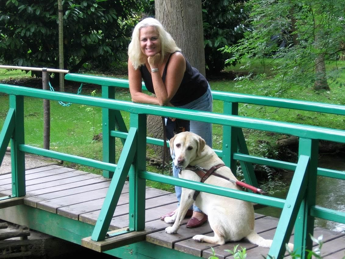 Moira and her dog Finnegan leaning against a green railing