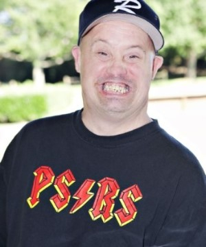 Man with Downs Syndrome supported by PSRS wearing a blue baseball cap and a PSRS Tshirt, looking at the camera with a big smile.