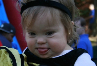 Toddler girl with Down syndrome in cheerleading costume at a past Buddy Walk event.