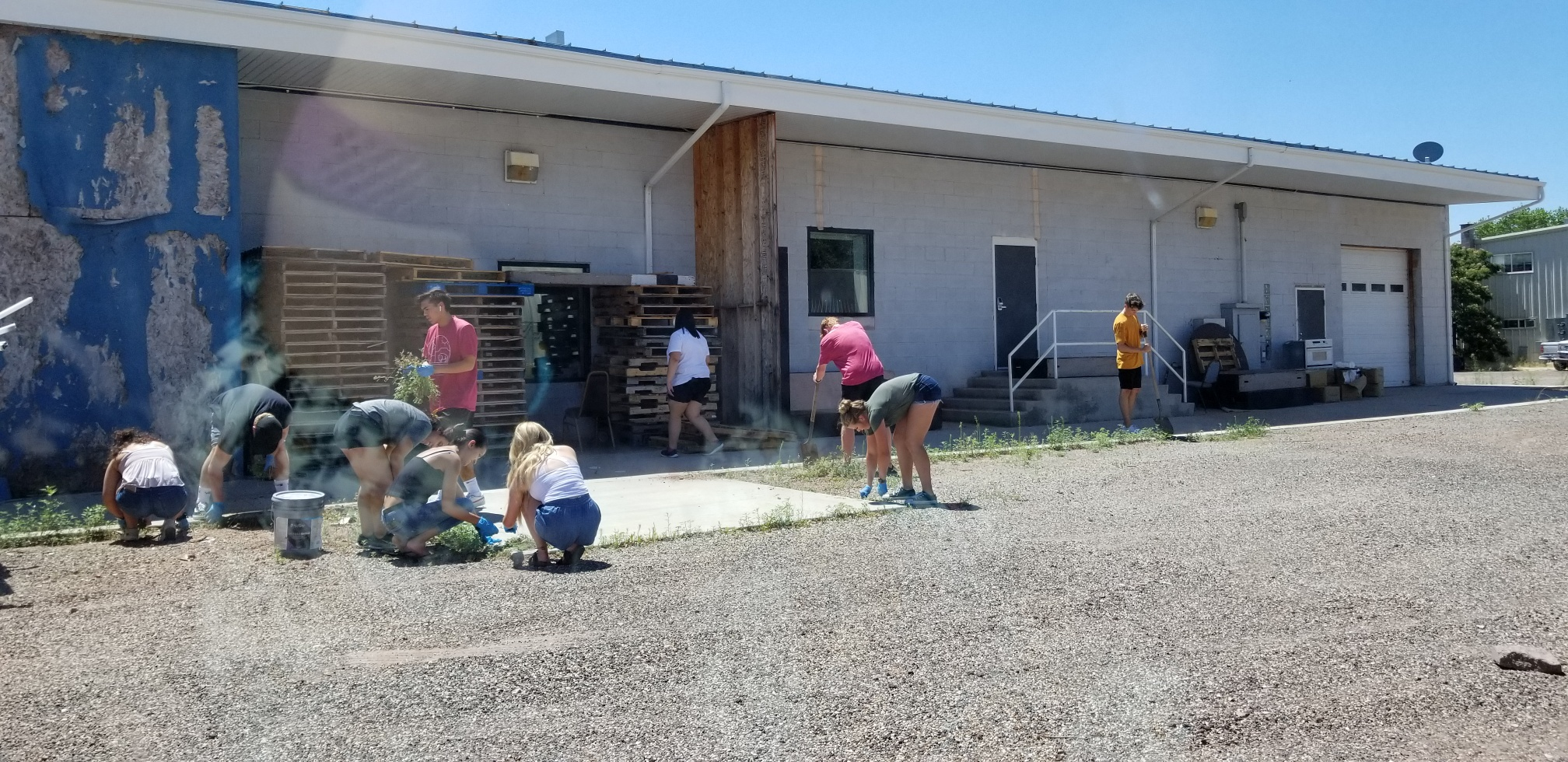 Volunteers improve the grounds of a health clinic in polygamist community