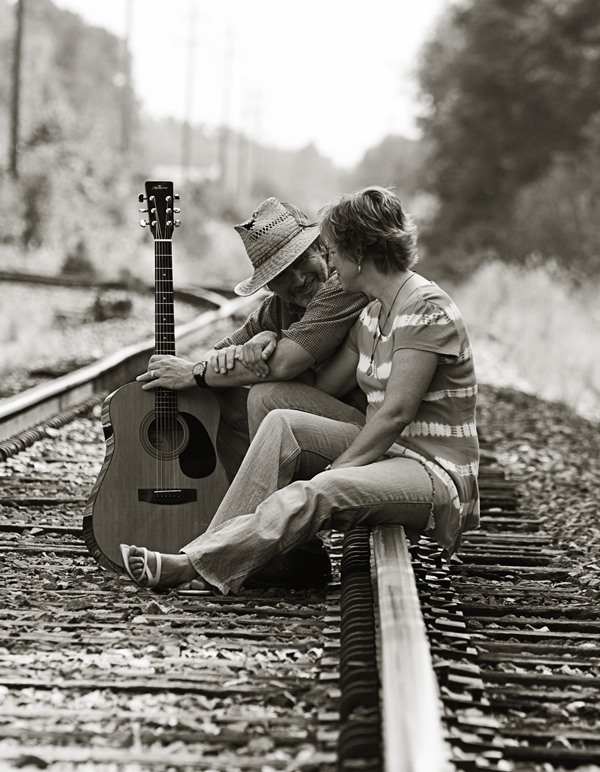 Two people sitting on railroad tracks holding a guitar