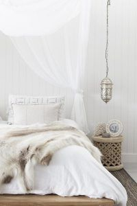 Bedroom furniture with all white bedding and faux fur blanket.