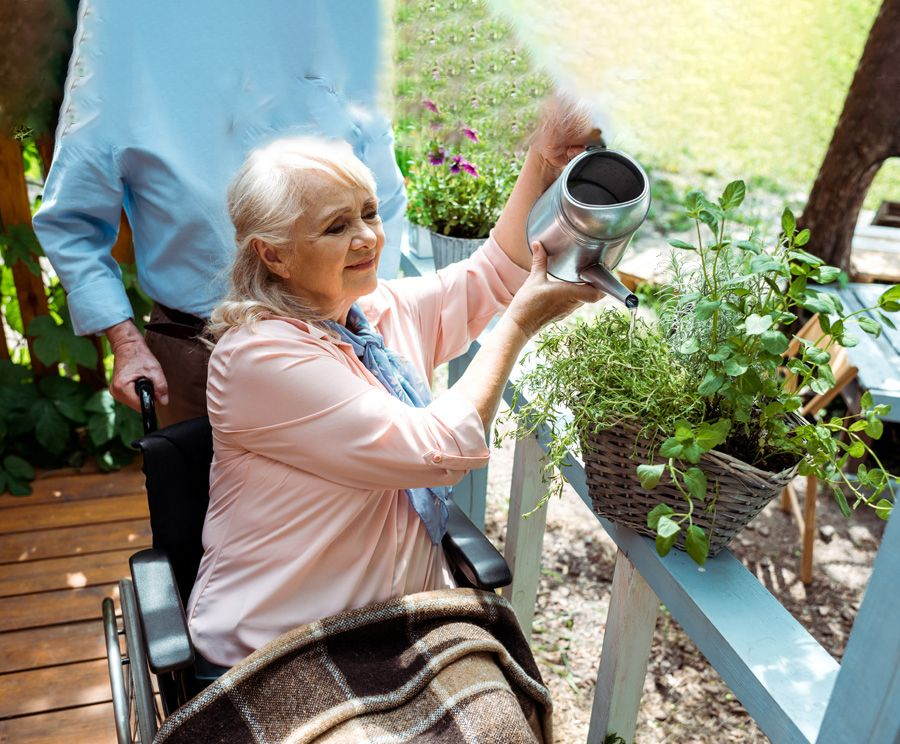 Gently smiling older woman in wheelchair is watering her plants outside on her deck. A man is pushing her wheelchair.