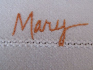 The name Mary embroidered on a table cloth thrifted from Goodwill.