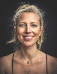 Kathryn Tucker, Executive Director of Arkansas Cinema Society - This pohot is a headshot. She smiles at the camera. Her blonde hair is in a an informal updo and she wears large gold scarab beetle earrings.