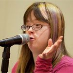 A young woman looks outward as she speaks into a microphone with left hand raised at face level.