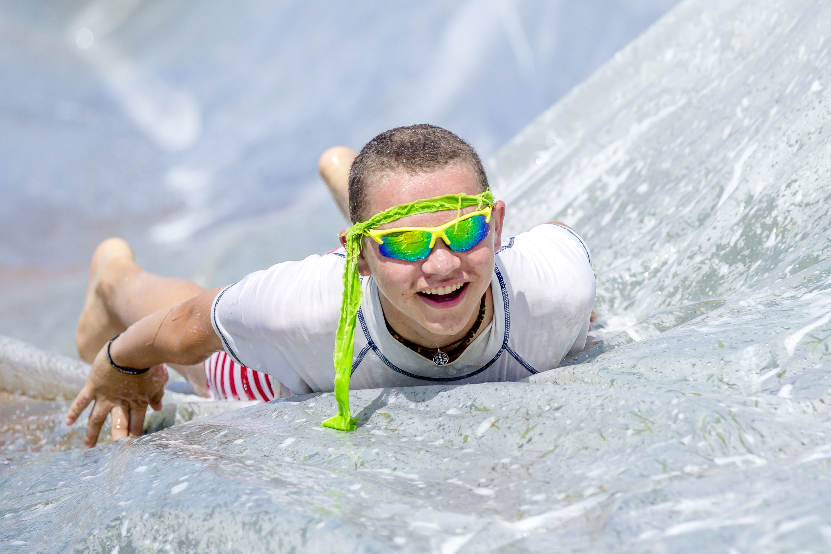 A camper slides down the slip-n-slide.
