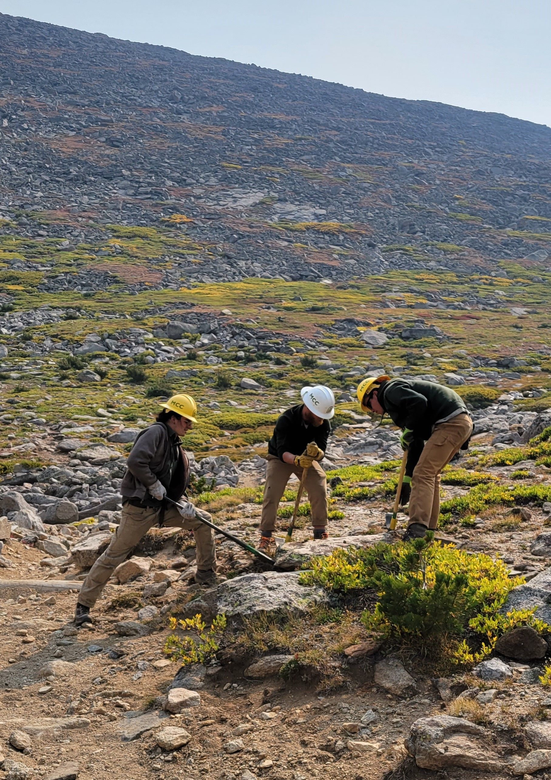 A crew works on a trail to remove blasted rock