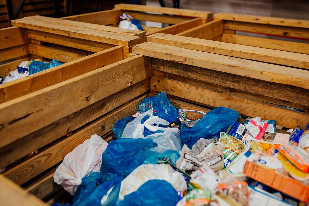 Four crates with plastic bags of food for sorting.