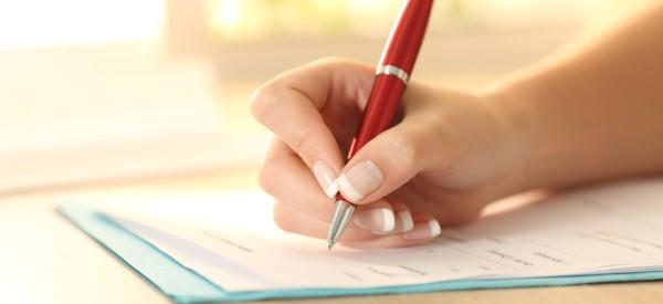 Woman filling out a paper survey with a pen