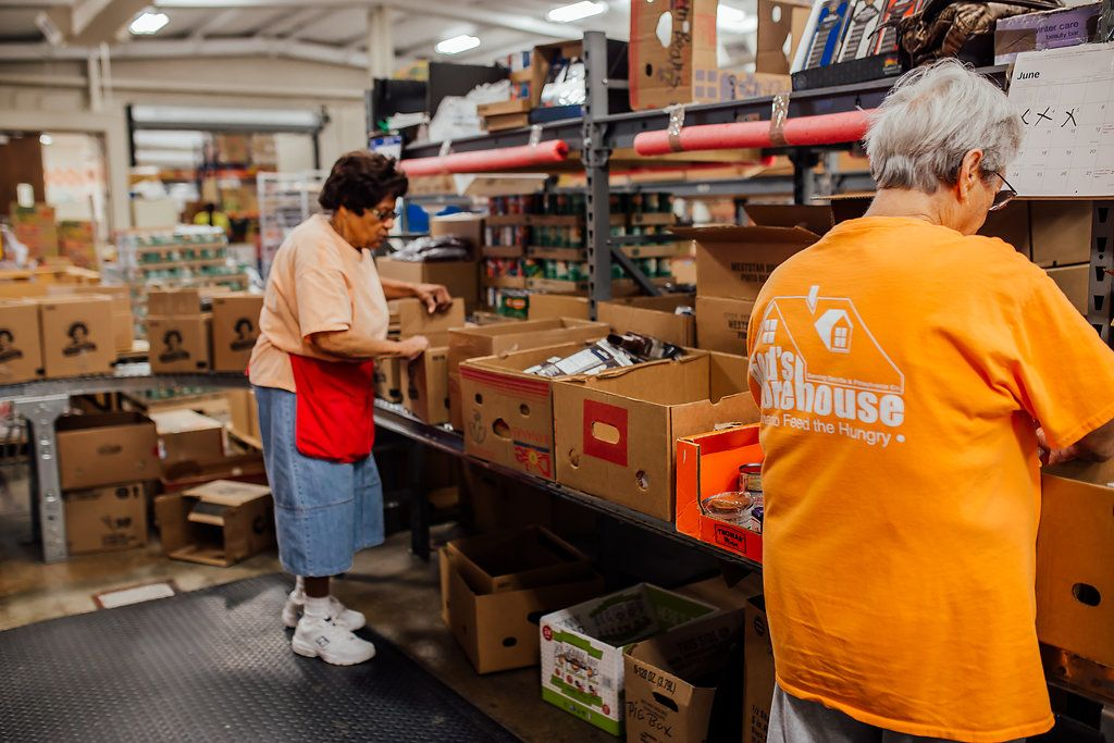 Two women sorting food on the food sorting line for distribution