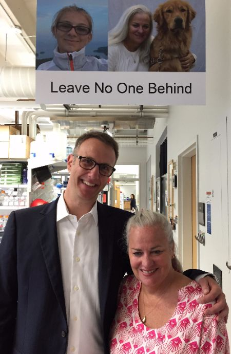 """Photo of Moira Shea and Mark Dunning at the Usher Syndrome Research Lab in Iowa, in front of a sign with pictures of Bella Dunning and Moira and her dog that reads """"Leave No One Behind"""""""