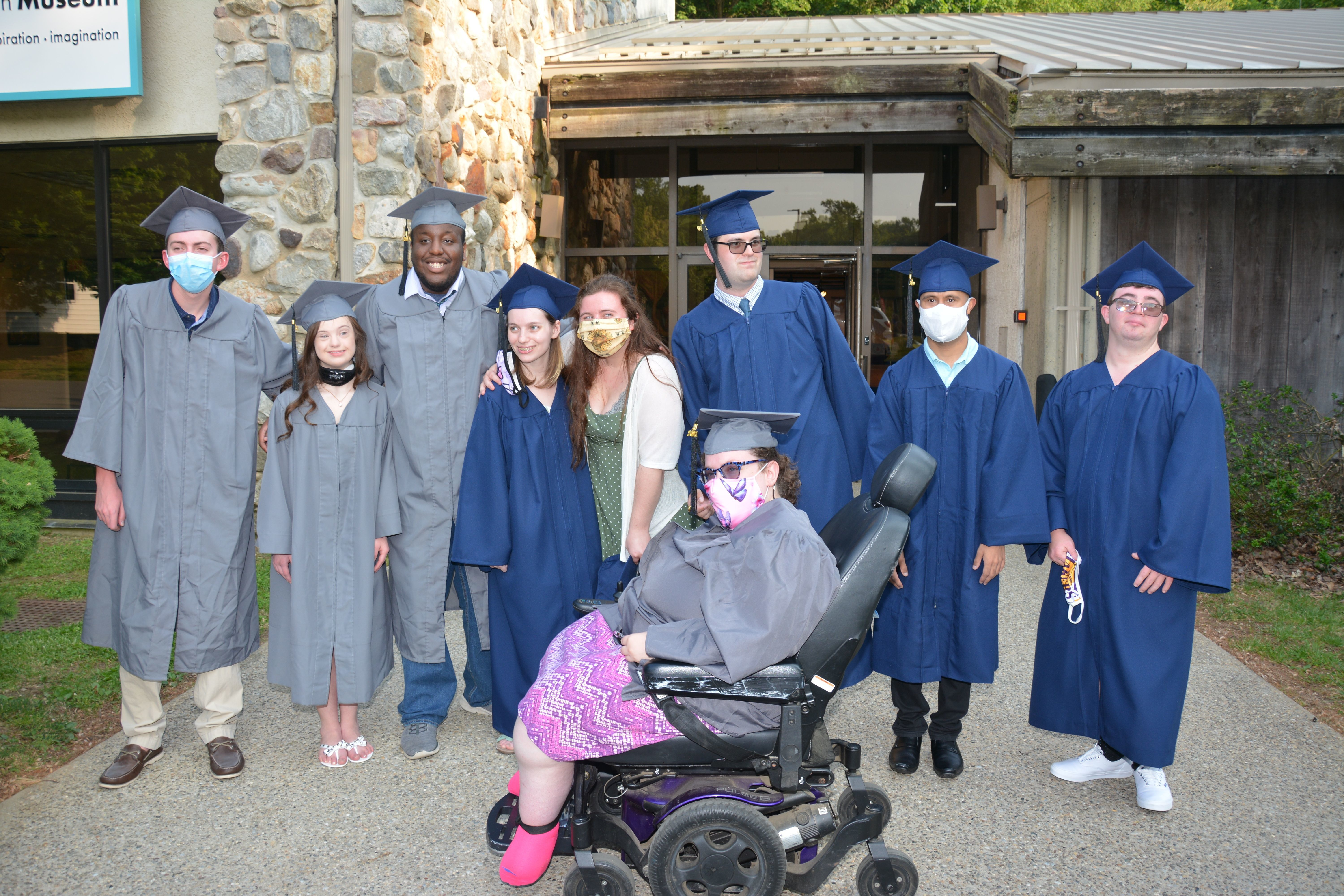 2020-2021 Kach Graduates stand in cap and gown on graduation day.