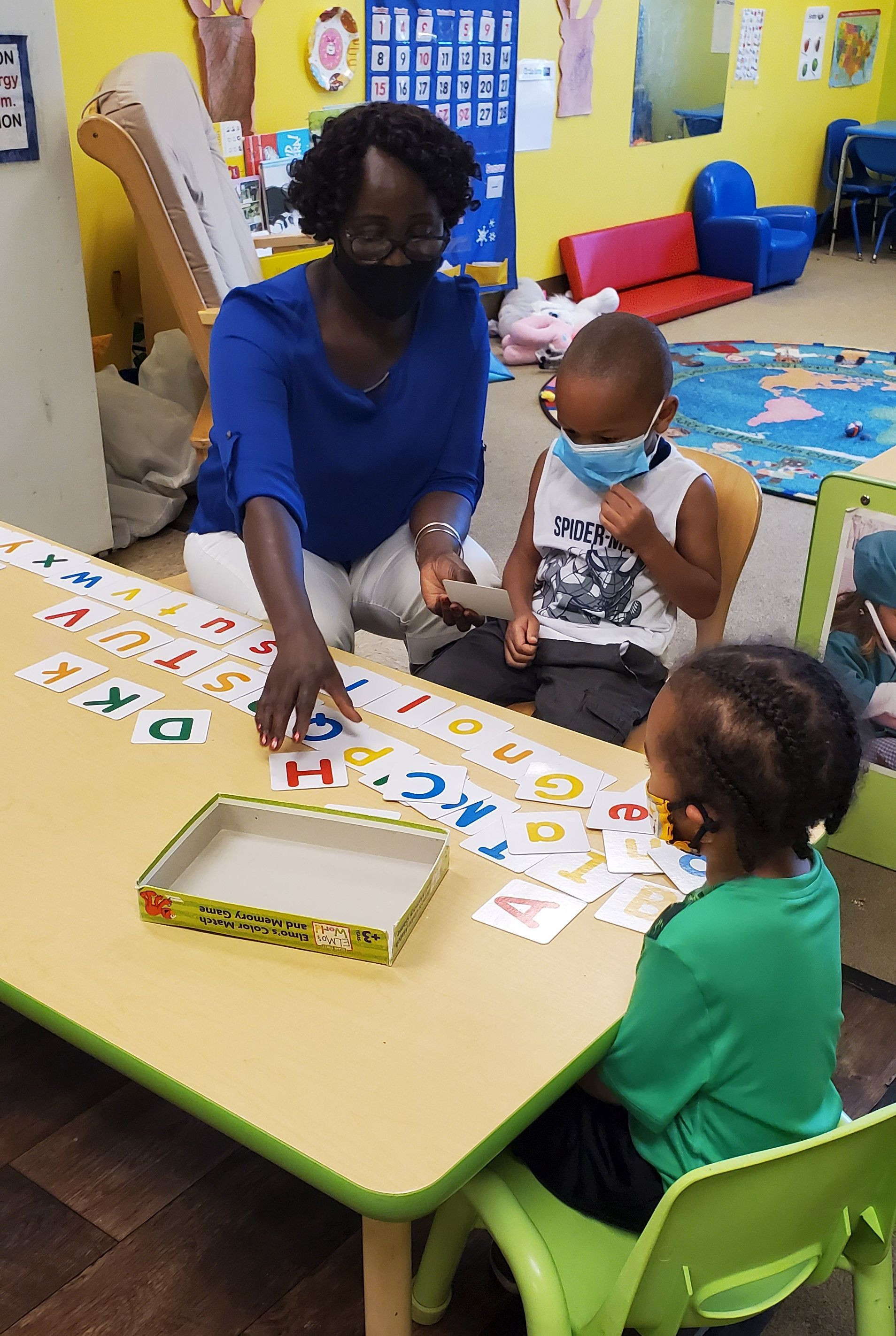 A teacher is sitting at a table with two small children and shows them flashcards with letters of the alphabet.