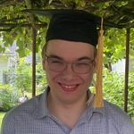 A young man smiles and stands under a pergola with college graduation cap.
