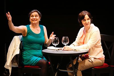 MURDER by Bekah Brunstetter (L to R) Anita is wearing a teal dress with her hands in the air & Pamela is wearing a white sweater and she's sitting at the dinner table with two empty wine glasses, looking away.