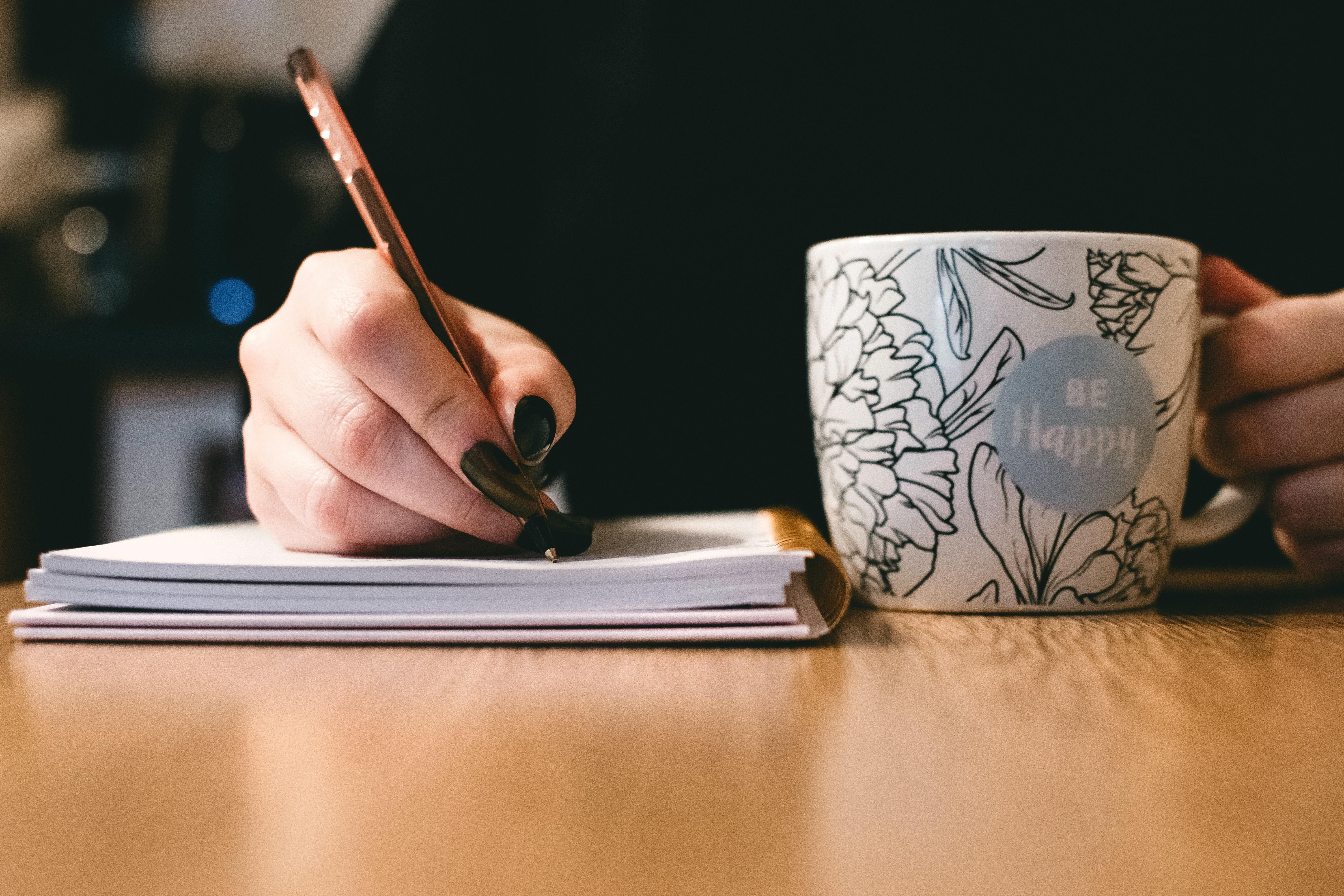A closeup of a woman's hand writing in a notebook next to a coffee mug.