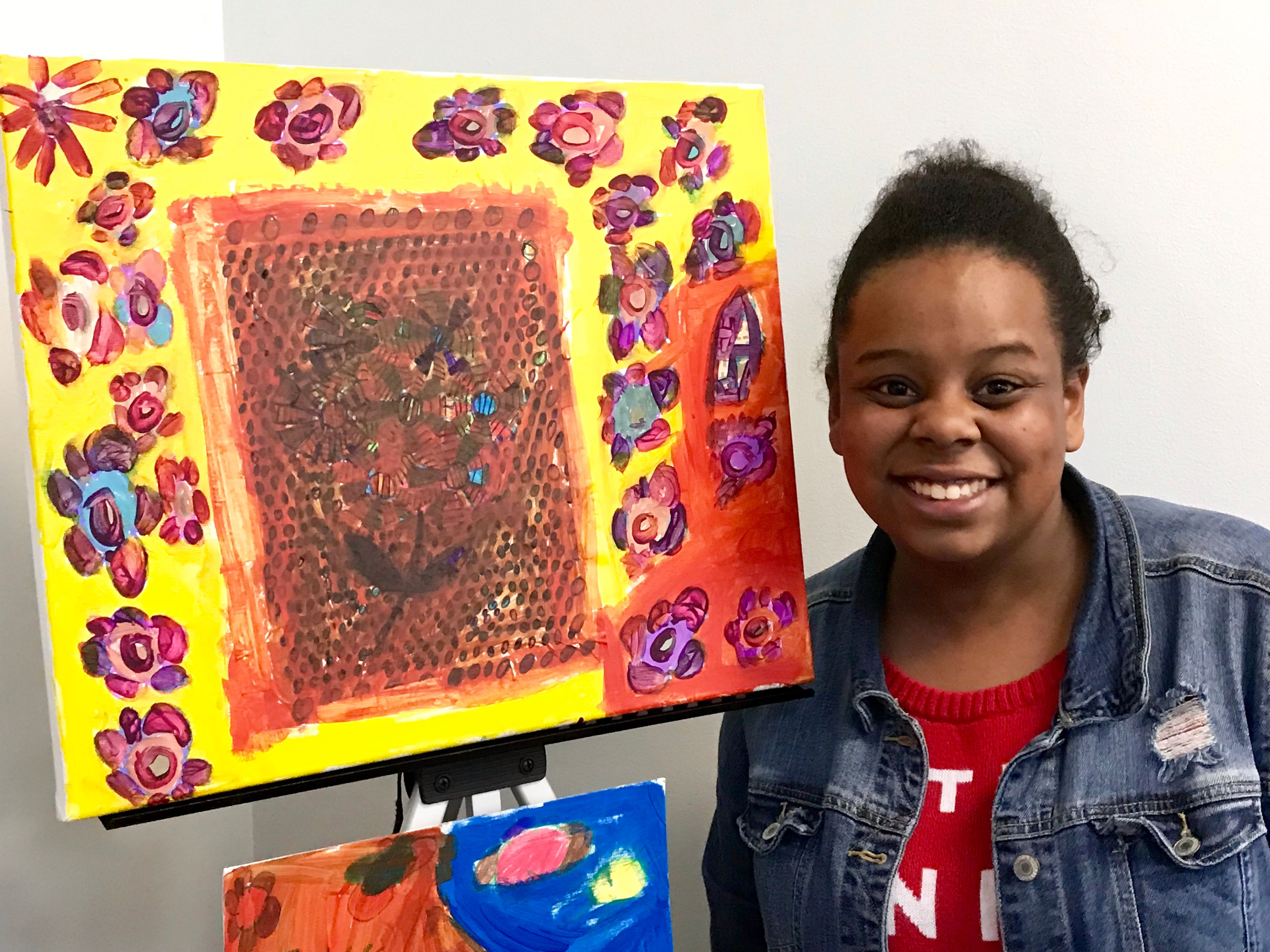 Cassie stands next to her original artwork on display during an exhibit