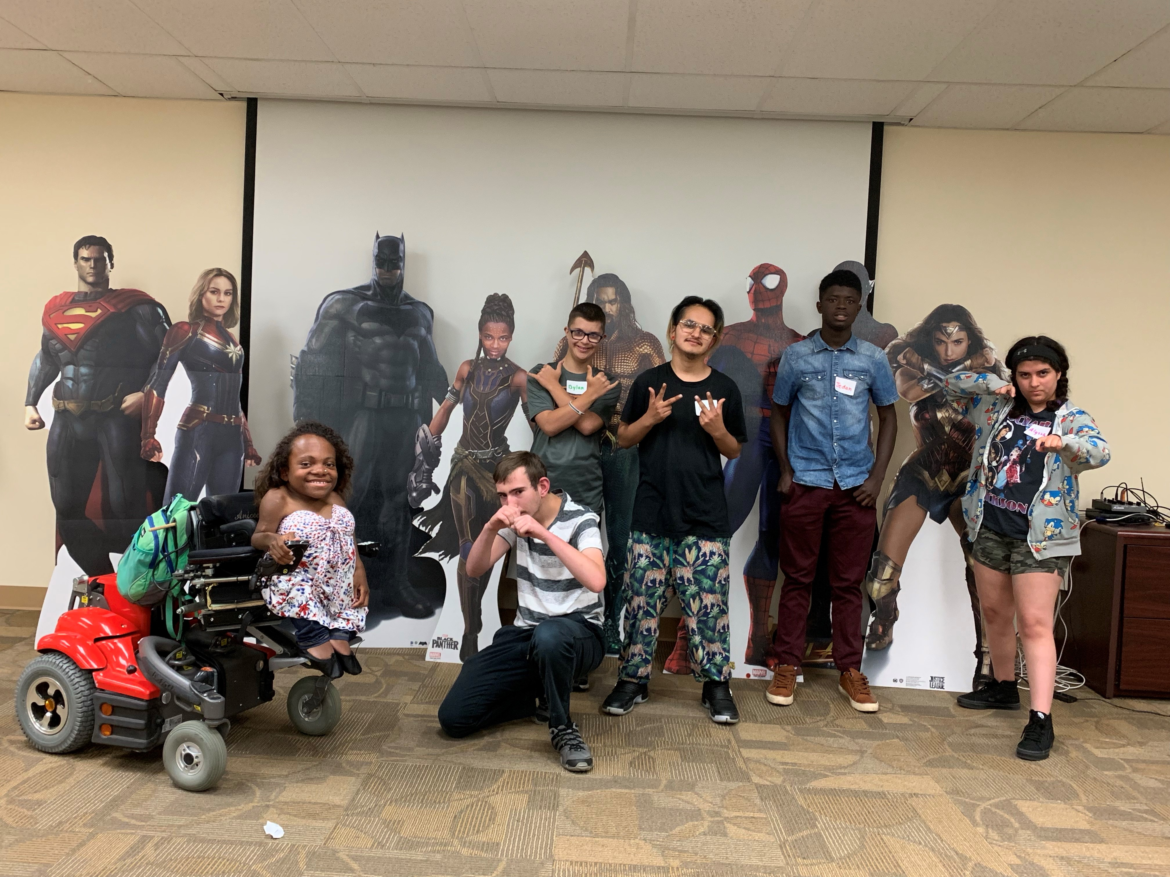 A group of teens pose with superhero cut outs at The Arc's offices