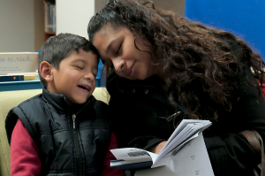 A mom and son read together at LPS.
