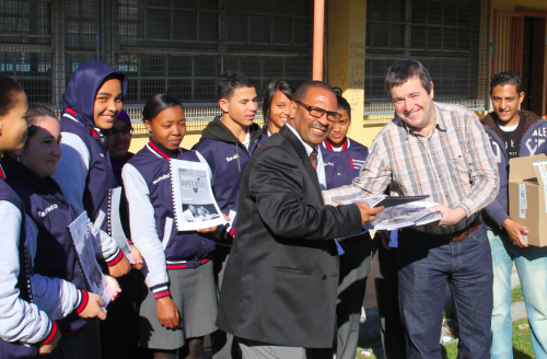 Rob Brickhill and Dean Mostert from Minuteman Press handing over the books to Mr Peters (acting principal) and some of the matrics from Silverstream Secondary School.