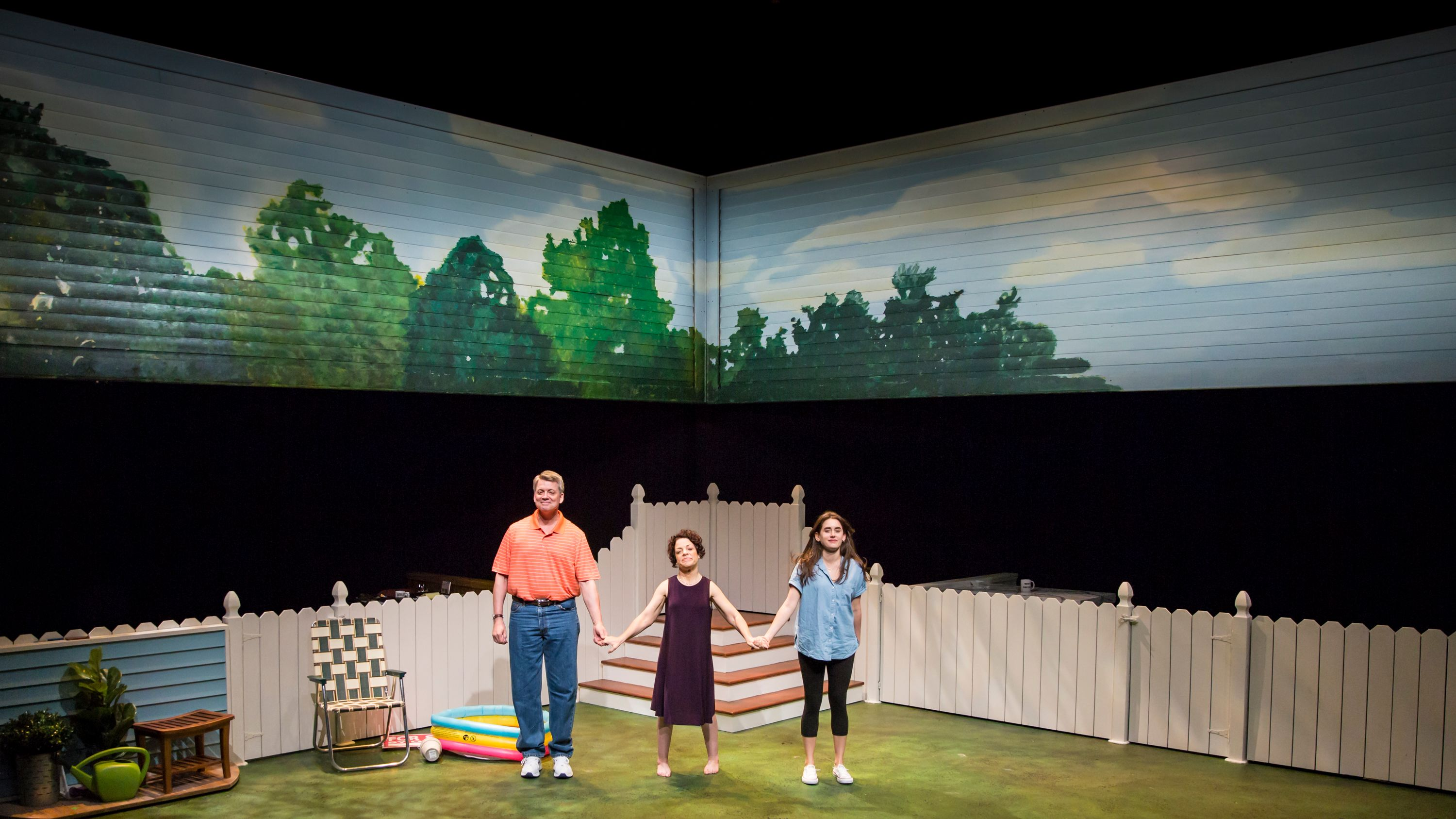 PUBLIC SERVANT-2019. (L to R) Chris Coffey, Christine Bruno & Anna Lentz. A group of actors are about to bow. They are standing on the a stage and in the background we see a backyard setting with a white picket fence and a blow up pool.