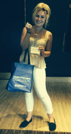 A picture of Molly Watt holding the USH2014 tote and name badge