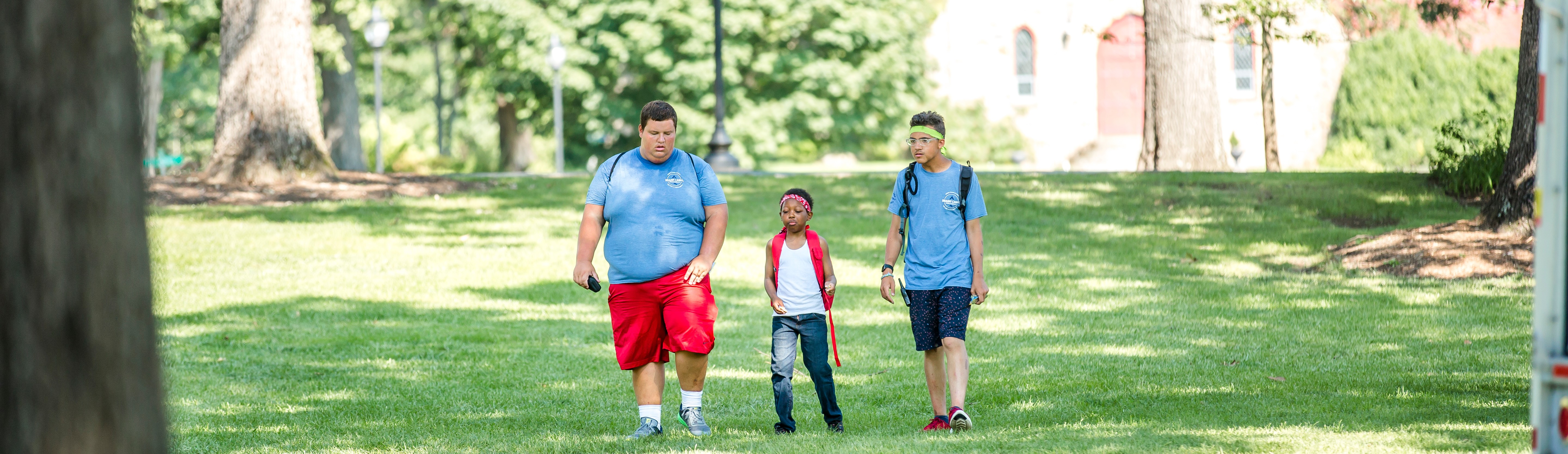 Two counselors walk with a young camper.