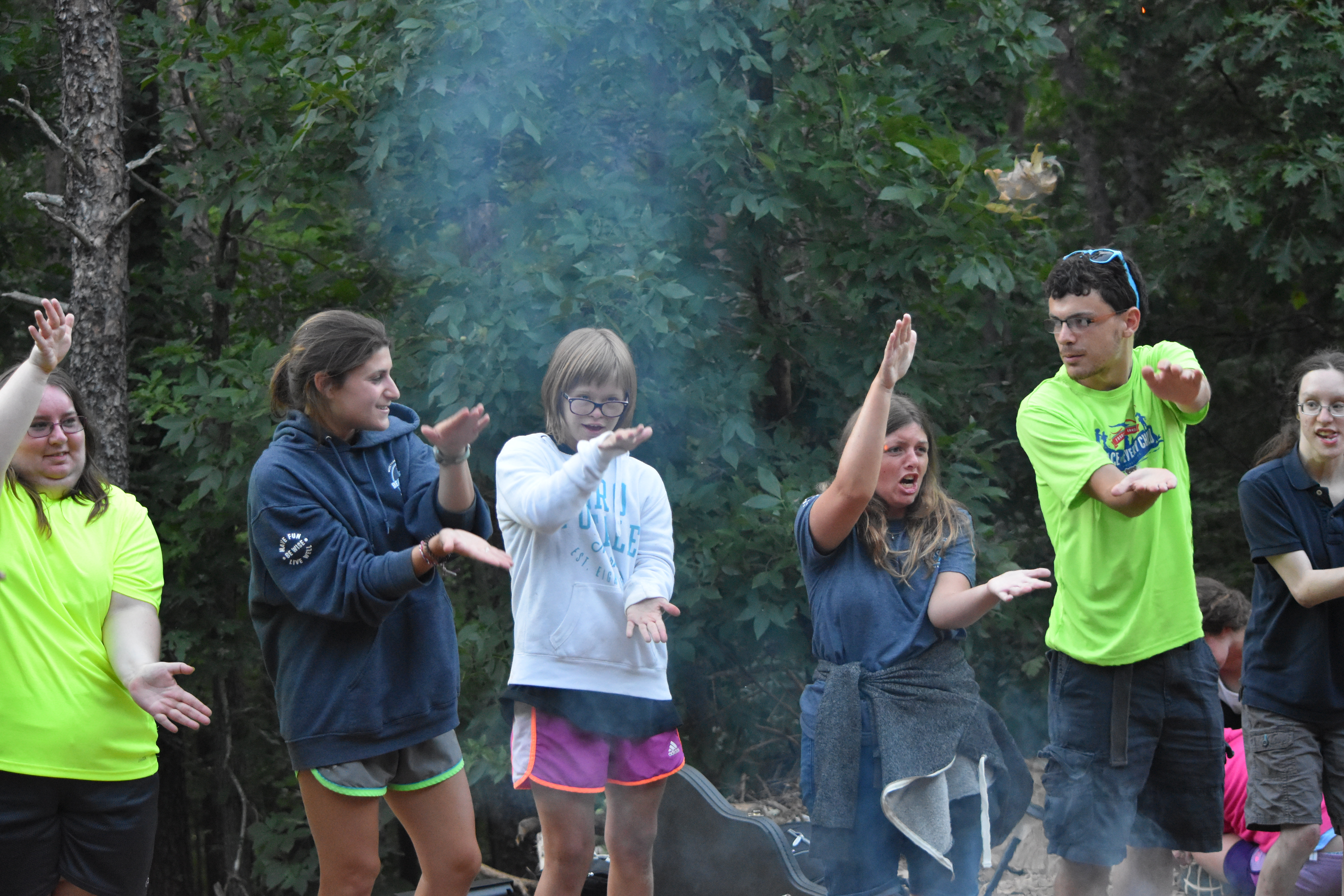 Campers and counselors sing songs by a campfire.