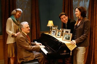 The majority of the group are standing around a piano and singing. George is sitting at the piano and playing it while Melanie is resting her hand on his shoulder.