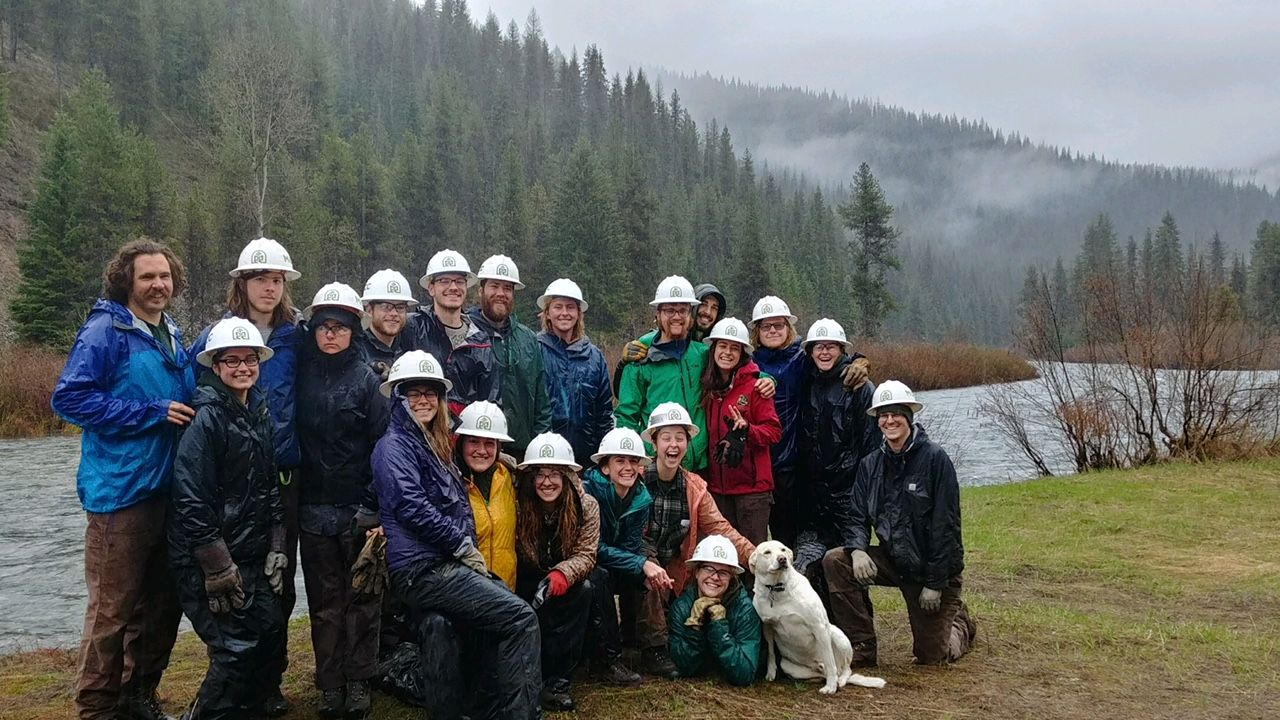 several crew members wearing white MCC helmets and rain gear up by the mountain but are smiling in the great outdoors