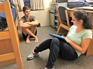 Two students sit on floor in dorm room chatting